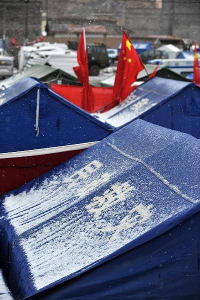Snow sleet are seen on several makeshift tents in Yushu County, northwest China Qinghai Province, April 20, 2010. The quake-hit area was hit by snow and rainfall on Tuesday. (Xinhua/Hou Deqiang)