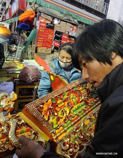 A customer selects a traditional container symbolizing a good harvest at a store in Lhasa, capital of southwest China's Tibet Autonomous Region, Feb. 6, 2012. Local residents of Lhasa started preparing food and home decorations to greet the coming Tibetan New Year, which falls on Feb. 22 this year. People of Tibetan ethnic group are able to enjoy two long holidays in 2012 to celebrate Chinese Lunar New Year and Tibetan New Year respectively. [Photo by Chogo/Xinhua]