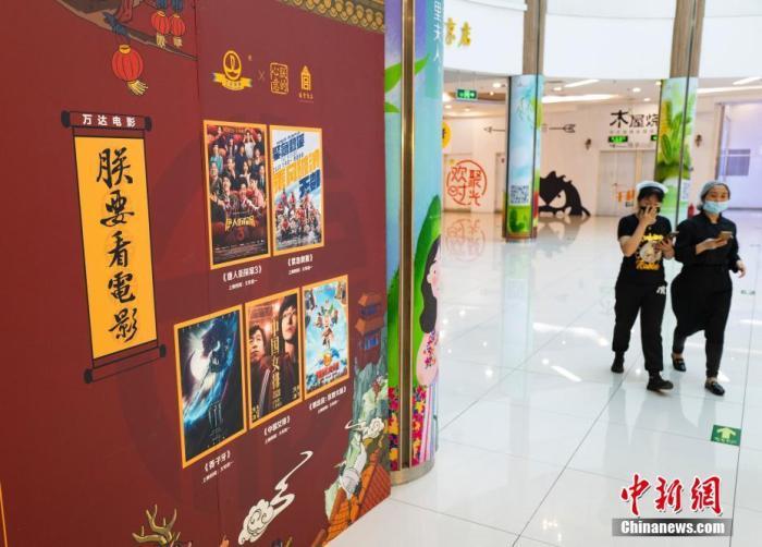 5月9日,行人从北京市朝阳区一家尚未恢复营业的电影院的宣传板前经过。中新社记者 侯宇 摄