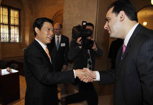 ChineseViceCommerceMinisterZhongShanisgreetedbyanunidentifiedpersonwhileattendingthebreakfastmeetingattheU.S.ChamberofCommerceinWashington,D.C.,capitaloftheUnitedStates,March24,2010.(Xinhua/ZhangJun)