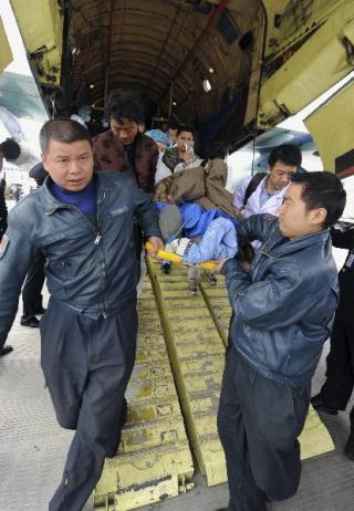 Pilots carry Cering Wende's wife out of the cabin of a cargo-transport plane at Xining Airport in Xining, capital of northwest China's Qinghai Province, April 19, 2010. A total of 14 Tibetan people with serious injuries were transported by a military cargo-transport plane to Xining for medical treatment on Tuesday. Tibetan resident Cering Wende who accompanied his wife and two daughters, all seriously injured, during the flight expressed his thankfulness to the pilot for many times. (Xinhua/Shen Ling)