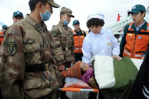 Rescuers carry an injured to an aircraft at an airport in quake-hit Yushu County, northwest China's Qinghai Province, April 22, 2010. The injured people were continually transported by aircraft from quake-hit Yushu County to Xining, capital of Qinghai, on Thursday. (Xinhua/Fan Changguo)