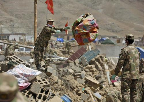 Chinese armed police soldiers help local residents to excavate usable things in quake-hit Yushu County, northwest China's Qinghai Province, May 1, 2010. (Xinhua/Shen Bohan)