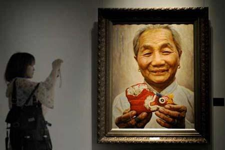 A visitor takes a photo of a painting by Li Zijian during an exhibition entitled