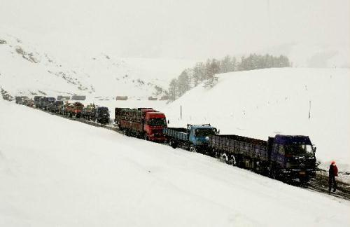 Vehicles move in the snow on the road in Hami Prefecture, northwest China's Xinjiang Uygur Autonomous Region, May 16, 2010. Influenced by strong cold wave, the north areas of Hami City along the Tianshan Mountain are hit by snowfall from Saturday to Sunday. (Xinhua/Polat)