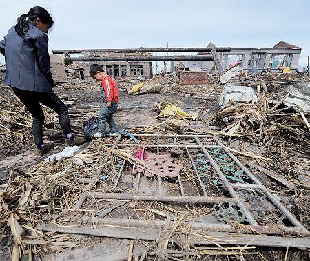 Villagers in Cuihua, Northeast China's Heilongjiang Province, stand in front of their damaged homes Sunday after a tornado and hailstorm struck the area Saturday, leaving seven people dead and 98 injured. (Xinhua)