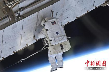 Atlantis crewmen Garrett Reisman and Stephen Bowen conducted a spacewalk, the first of three scheduled for this week, to install a spare antenna on the International Space Station on May 17. (Photo: chinanews.com)