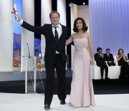 Director Xavier Beauvois (L) reacts on stage next to actress Salma Hayek after he won the Grand Prix award for the film Des Hommes et des Dieux (Of Gods and Men) during the award ceremony of the 63rd Cannes Film Festival May 23, 2010.(Xinhua/Reuters Photo)