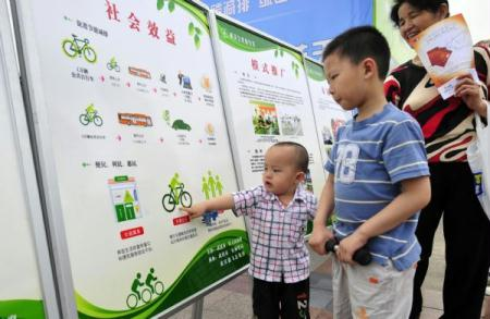 Two children look at an publicity poster board at an activity on environmental protection in Wuhan, central China's Hubei Province, June 5, 2010. World Environment Day was marked amid various programs on Saturday around China. (Xinhua/Hao Tongqian)