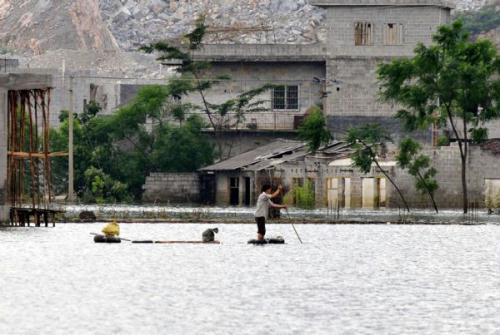 AresidentrowsaraftinChengjiangTownofYaoAutonomousCountyofDu'an,southwestChina'sGuangxiZhuangAutonomousRegion,June7,2010.FloodstillremainsinsomepartsofDu'anonJune7,sevendaysafterheavyrainstormskilled38people.(Xinhua/HuangXiaobang)