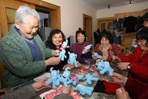 """王逢老人(左一)和老姐妹们展示她们为孤残儿童编织的""""海宝""""。新华社记者刘颖摄"""