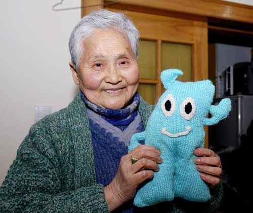 """王逢老人展示她为孤残儿童编织的""""海宝""""。新华社记者刘颖摄"""