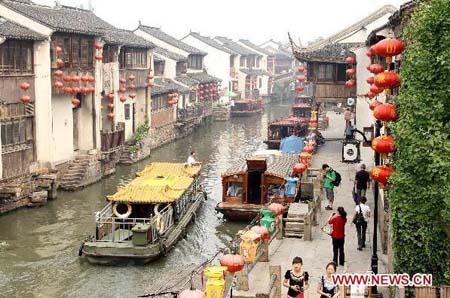 "Photo taken on June 13, 2010 shows sightseers either taking the mat-covered barges or walking on the bank enjoying the landscape on the Shantang Street, nicknamed as the ""Oriental Water Street"", which has been listed on the 2nd batch of Chinese Historical and Cultural Famous Streets on June 12, in Suzhou City, east China's Jiangsu Province. So far, there have been two archaic streets with typical traditional feature in Suzhou on the list of Chinese Historical and Cultural Famous Streets, the other one is Pingjiang Road. [Photo:Xinhua]"