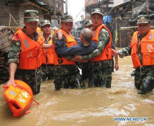 Soldiers transfer an old man trapped by the flood water at Songxi Town of Qingliu County, southeast China's Fujian Province, June 18, 2010.(Xinhua/Lu Lijie)