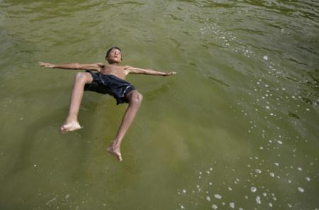 A boy jumps into a pond to beat the heat on a hot day in New Delhi June 23, 2010. The maximum temperature recorded on Wednesday was approximately 44 degrees Celsius (111degrees Fahrenheit) in New Delhi, according to India's metrological department.(Xinhua/Reuters Photo)