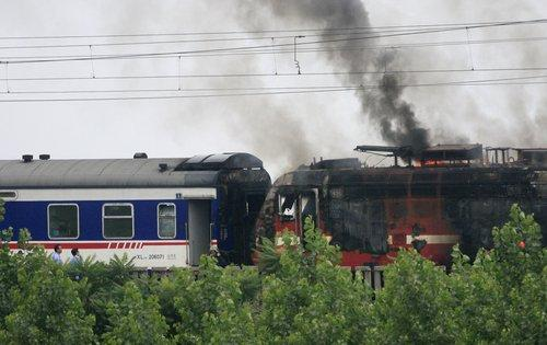 The engine of a passenger train catches fire on the railway line between Qingdao and Jinan in East China's Shandong province on June 30, 2010. The blaze was put out by local firefighters, all 1,000 passengers on board were safely evacuated and no injuries reported. The cause of the fire is under investigation. The train, T162, is bound for Guangzhou, South China's Guangdong province from Qingdao of Shandong.[Photo/CFP]