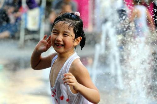 A girl plays at a fountain in Shenyang, capital of northeast China's Liaoning Province, on July 3, 2010. Hot weather swept most regions in northern, central and southern China these days, with temperature of some regions soaring to 39 degrees celsius. (Xinhua/Zhang Wenkui)