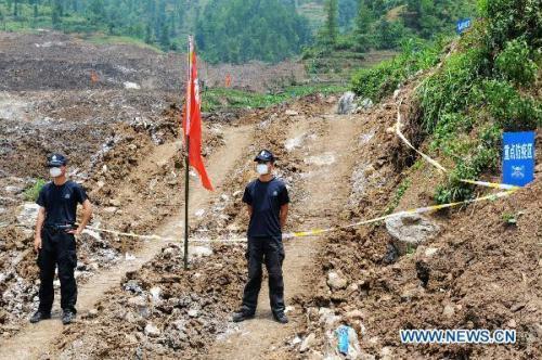 Policemenstandguardatthelandslide-hitDazhaiVillage,GuanlingCountyofsouthwestChina'sGuizhouProvince,July4,2010.RescuersSundaygaveupsearchingformoresurvivors,sixdaysafterarain-triggeredlandslideburied99peopleinasouthwestChina'svillage,citingmountingconcernstoheadofftheoutbreakofdiseaseaswellastheslimchanceanyonecouldhavesurvivedafternearlyoneweek.(Xinhua/LiuXu)