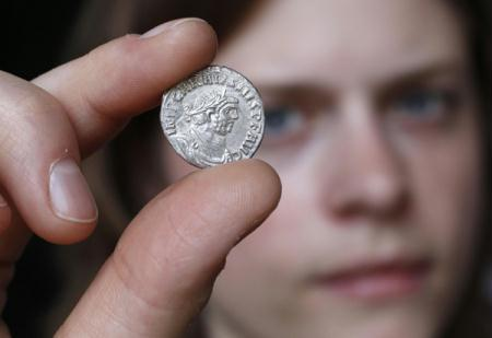 Janina Parol of the British Museum holds a rare silver denari coin in London July 8, 2010. One of the largest hoards of Roman coins ever found in Britain has been unearthed in a field in Somerset, southwest England, by an amateur treasure hunter with a metal detector. The stash of some 52,000 mostly bronze coins dating from the third century AD was buried in a large, well-preserved pot close to the picturesque town of Frome. It has yet to be valued.(Xinhua/Reuters Photo)