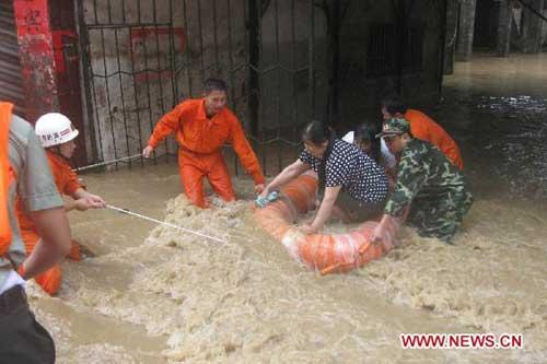 Fire fighters evacuate residents in Youyang County of Chongqing Municipality, southwest China, July 9, 2010. The electricity supply was interrupted by a heavy rainfall in Youyang on Friday. Local fire brigade dispatched 65 fire fighters to evacuate over 1,000 residents and rescue 215 trapped people. (Xinhua)
