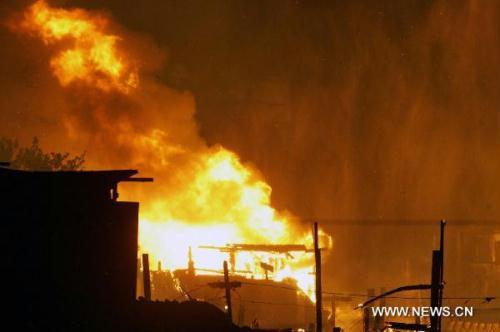 Fire rages in eastern Sao Paulo, Brazil, July 11, 2010. A huge fire was under control after it burnt out injuring two on Sunday evening.(Xinhua/Sao Paulo News Agency)
