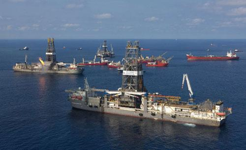 "The Transocean Discoverer Inspiration (foreground) arrives at the site of the Deepwater Horizon to install a ""capping stack"" on the well in the Gulf of Mexico, in this handout photograph taken on July 10, 2010 and released on July 11, 2010. (Xinhua/Reuters Photo)"