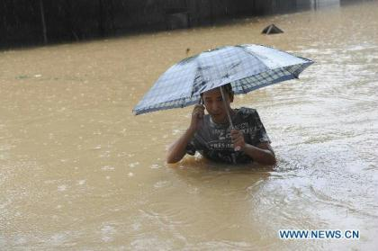 A citizen calls on a waterlogged road in Anqing, east China's Anhui Province, July 13, 2010. Heavy rainfall hit Anqing on Tuesday, causing severe flood in the city. Some 600 soldiers and more than 20 speed boats were dispatched to rescue people trapped by the flood. More than 20,000 residents have been transfered to safe places. (Xinhua/Xu Guokang