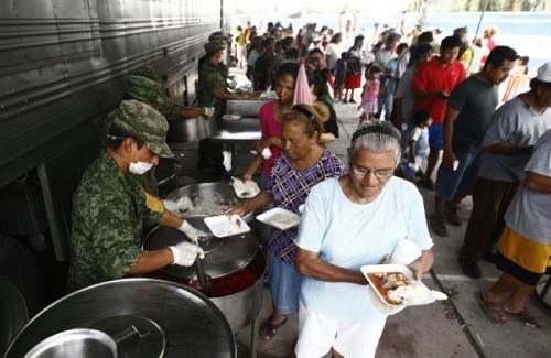 Soldiers distribute food at a military dining hall for victims of Hurricane Alex in its aftermath, in the suburb of Santa Catarina, neighbouring Monterrey, Mexico, July 9, 2010. (Xinhua/Reuters Photo)