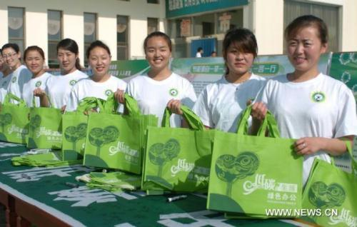 Volunteers of the Institution Energy-saving Week send out recyclable shopping bags to the public in Hohhot, capital of north China's Inner Mongolia Autonomous Region, June 12, 2010. The 2010 Inner Mongolia Institution Energy-saving Week was launched on Saturday. In the following week, institutions in Inner Mongolia will advocate green office and low-carbon life with a series of activities like promoting green traffic, boycotting excessive packaging and experiencing energy-lack life.(Xinhua/li yunping)