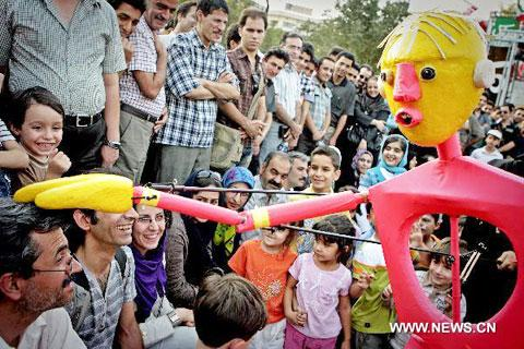A German puppet plays with visitors during the 13th Tehran International Puppet Theater Festival in Tehran, capital of Iran, July 22, 2010. The six-day-long festival opened here on Thursday. (Xinhua/Ahmad Halabisaz)