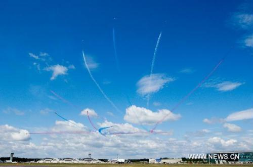 The RAF Red Arrows perform during an air display on the final day of the Farnborough Airshow in Farnborough in southern England July 25, 2010. (Xinhua/Tang Shi)