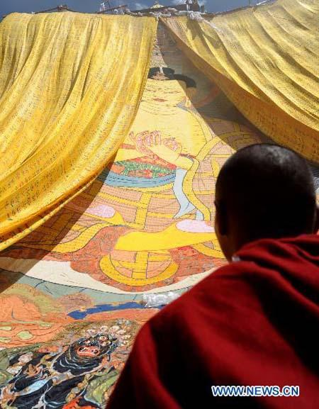 A monk looks at the thangka during the annual thangka unfurling ceremony at Ganden Monastery in Lhasa, capital of southwest China's Tibet Autonomous Region, July 25, 2010. Built along the slopes of the Wangbori Mountain, Dagze, Lhasa, the Ganden Monastery was the original monastery of the Gelug sect of Vajrayana Buddhism, founded by Tsongkhapa in 1409. Thousands of pilgrims gather here each year to worship a huge appliqued thangka that depicts the Buddha during the festival, one of the grandest buddhist ceremonies in Tibet. (Xinhua photo)
