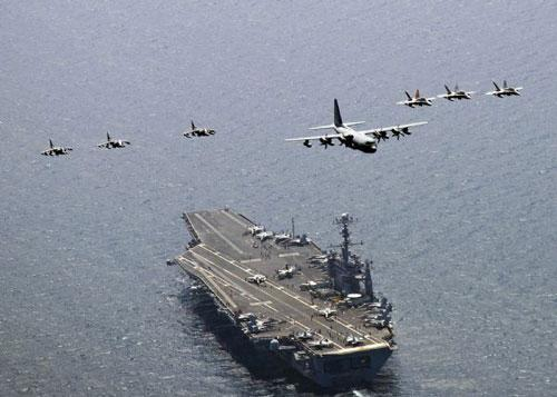 A U.S. Marine Corps C-130 Hercules aircraft leads a formation of F/A-18C Hornet strike fighters and A/V-8B Harrier jets over the aircraft carrier USS George Washington (CVN 73) in the East Sea of Korea, July 27, 2010. (Xinhua/Reuters)