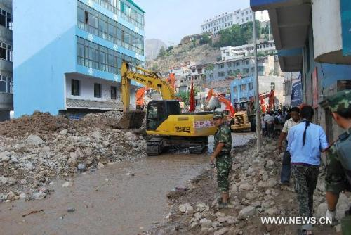 Soldiers restore the road in the landslides-hit Zhouqu County, Gannan Tibetan Autonomous Prefecture in northwest China's Gansu Province, Aug. 10, 2010. After two days' working, the rescuers resumed the traffic to the downtown of Zhouqu County. (Xinhua/Pi Feng)