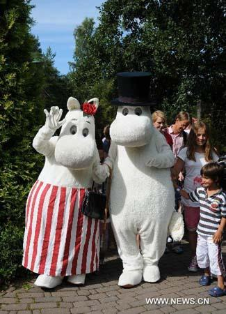 "Staff of Moomin World dressed up as Moomin characters welcome visiting children at Moomin World on a small island facing Naantali, southwest coast of Finland, Aug. 5, 2010. The theme park Moomin World was built on the southwest coast of Finland, on a small island facing Naantali. The theme park was built basing on a series of children's books ""The Moomins "" written by Tove Jansson (1914-2001), a famous Finnish author and painter. The Moomins, main characters in the fairy tales, vaguely resemble hippopotamuses, lived in the Moominvalley where residents are in harmony with nature, were world-famous cartoon characters. (Xinhua photo)"