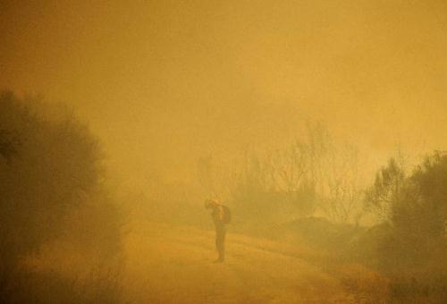 AmemberofthefirebrigadeworksaroundtheareawhereafireburnsinCualedro,nearOurense,Spain,August10,2010.(Xinhua/AFPPhoto)