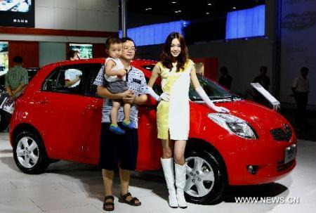 A man with a child in his arms poses for photos in an auto show in Beijing, capital of China, Aug. 12, 2010. The 4-day auto show kicked off on Thursday. (Xinhua/Gong Bing)