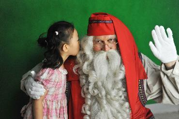 A child kisses the beard of Santa Claus.