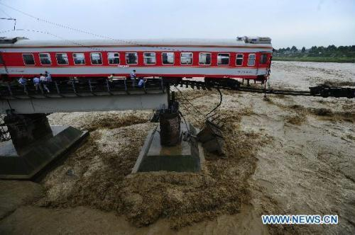 Two carriages of a passenger train fall into a river after floods destroyed the Shitingjiang Bridge on the Baocheng Railway in Xiaohan Town, Guanghan City of southwest China's Sichuan Province, Aug. 19, 2010. The train was traveling from Xi'an, capital of northwest China's Shaanxi Province, to Kunming, capital of southwest China's Yunnan Province. No casualties were caused and no people were missing as all the passengers were evacuated from the train before the carriages plunged into the river. (Xinhua/Jiang Hongjing)