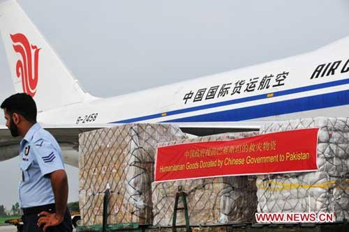 A guard stands beside humanitarian goods donated by the Chinese government at a military airport in Rawalpindi, Pakistan, Aug. 19, 2010. (Xinhua/Yan Zhonghua)
