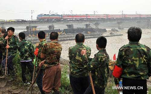 Workers look at a train running on the Baoji-Chengdu Railway in Xiaohan Township of Guanghan, a city of Sichuan Province, Aug. 20, 2010. (Xinhua/Jiang Hongjing)