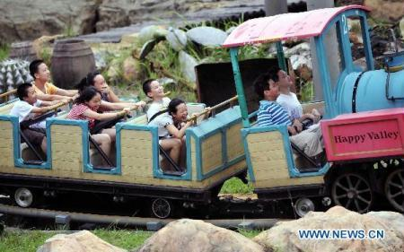 Photo taken on June. 1, 2010 shows children taking a toy train in the Happy Valley, an amusement park in Shenzhen, south China's Guangdong Province. From a little village three decades ago to one of the Cities of Design designated by UNESCO in Nov. 2008, the first in China, Shenzhen uplifts its cultural industry to the fourth pillar industry after Hi-technology, finance and logistics while the city's 30th anniversary as a Special Economic Zone comes around the corner on Aug. 26, 2010. (Xinhua/Chen Yehua)