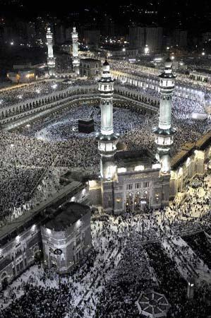 Muslim pilgrims pray inside the Grand Mosque, with the Mecca Clock lit up in the background, on the first day of the fasting month of Ramadan in Mecca August 11, 2010. (Xinhua/AFP Photo)