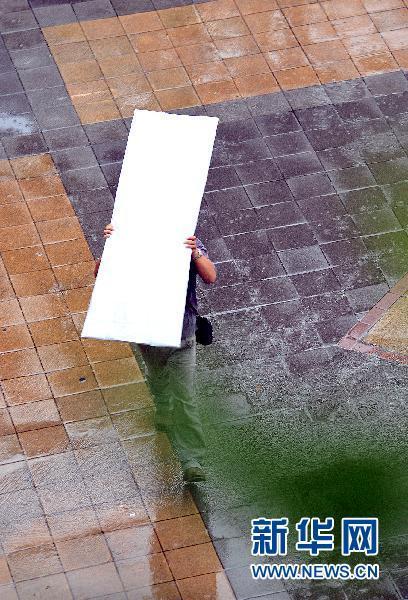 10月21日,一位路人用木板遮雨步行在台北街头. 新华社记者 何俊昌 摄