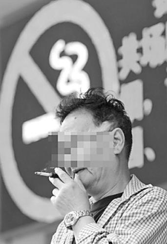 一位男士在广州红十字会医院大堂门口吞云吐雾,他背后的大屏幕上正反复播放禁烟警示。新华社发
