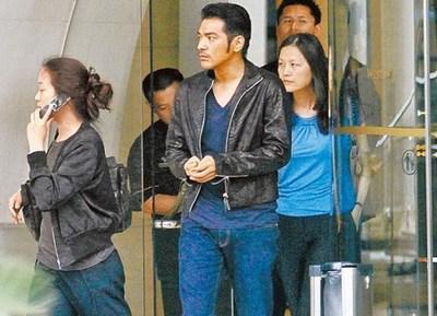 略显老态的金城武(中)日前在上海和两名女子进出酒店,其实右为经纪人姚宜君