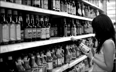 一名顾客在超市对比挑选山西老陈醋。本报记者王苡萱摄