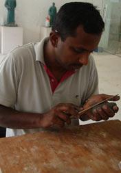 """印度艺术家Gopinath Subbanna(李小虎)在指导工作人员制作雕塑作品中的""""叶子"""""""