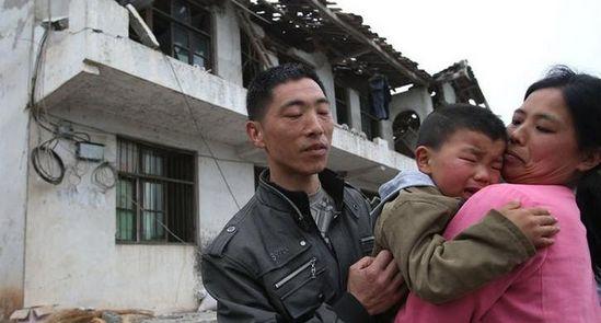 村民在自家塌掉的楼房前安慰哭泣的孩子。