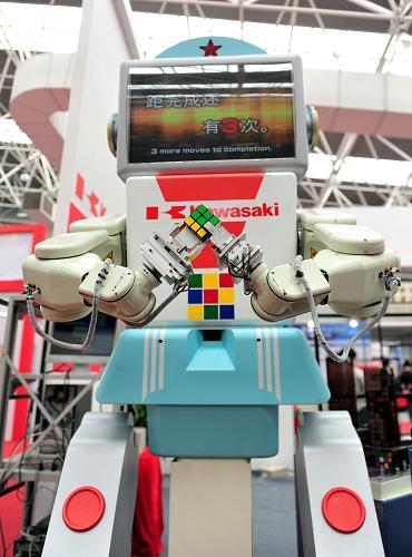 3月29日,一台机器人在首届中国国际进口产品博览会上拼魔方。新华社(王启明 摄)